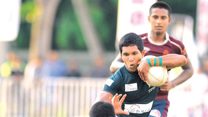 Isipathana's Chamod Fernando is being confronted by Science College  Full Back Supun Dilshan in their Singer schools under 19 Rugby match played at Havelock part yesterday which Isipathana won 29-24. Picture by Samantha Weerasiri