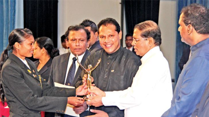 Nimali Liyanarachchi, the 2015 Asian Athletic Championship women's 800 metres bronze medalist receiving the Most Outstanding Sports Woman of the Year award from President Maithripala Sirisena and Sports Minister Dayasiri Jayasekara in the inaugural Presidential Sports Awards Ceremony held at the BMICH yesterday. Picture by Sudath Malaweera
