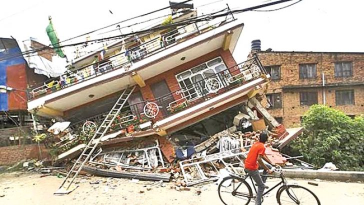 A cyclist observes the damage caused to a house by the April 2015 eattquake in Nepal. - AFP