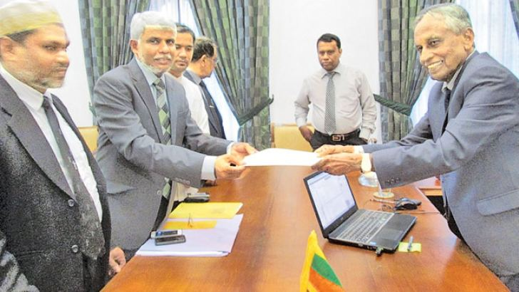 Eastern Province's Chief Minister Z. A. Nazeer Ahamed being sworn-in before Eastern Province Governor Austin Fernando