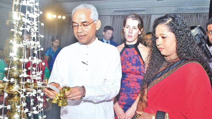 Special invitee Deputy Minister of Investment Promotions and Highways, Eran Wickramaratne lighting the oil lamp. Founder Chairperson, Women in Management, Sulochana Segera looks on. Picture by Siripala Halwala