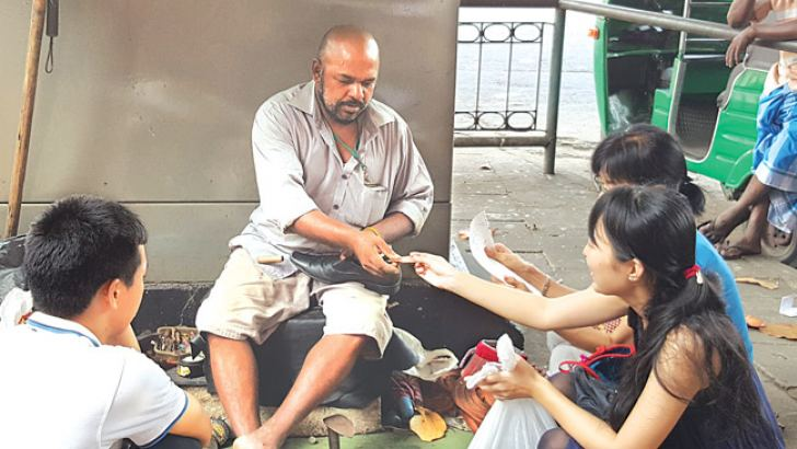 Chinese tourists watch as a shoe mender attends to their footwear in the Fort area. Picture by Shirajiv Sirimane