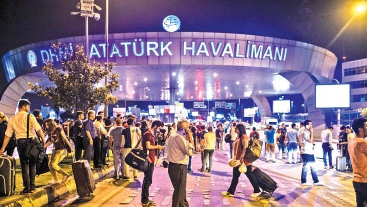 People stand outside the entrance as they leave the airport after two explosions followed by gunfire hit Turkey's largest airport of Ataturk in Istanbul on Tuesday.- AFP