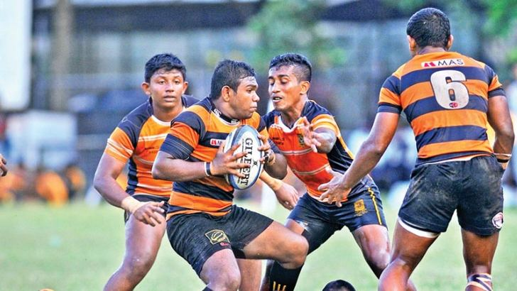 D.S. Senanayake College prop forward M.Siddique trying to barge away his way over from the Mahanama defenders, with support coming his way from flanker (Number 6) Inura Samarawickrama in their inter-schools rugby match played at Longden Place yesterday. Picture by Samantha Weerasiri
