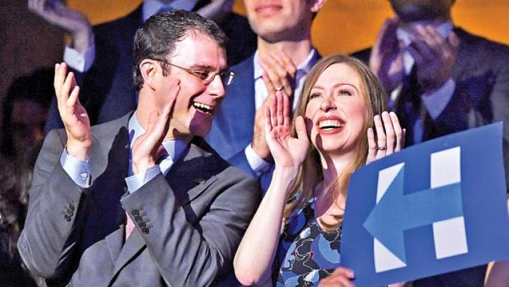 Chelsea Clinton and husband Marc Mezvinsky smile as Hillary Clinton appears on screen live during the second day of the convention.