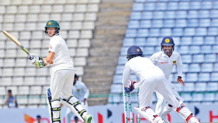 Australian captain Steve Smith is stumped by Dinesh Chandimal off Rangana Herath for 30 on the second day of the first Test against Sri Lanka at Pallekele Stadium yesterday. Pictures by Rukmal Gamage