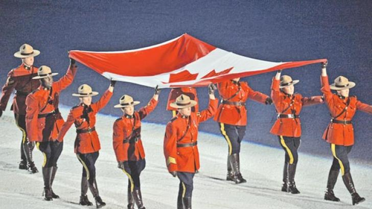 Members of the Royal Canadian Mounted Police carry the Canadian flag at a sporting event. - AFP