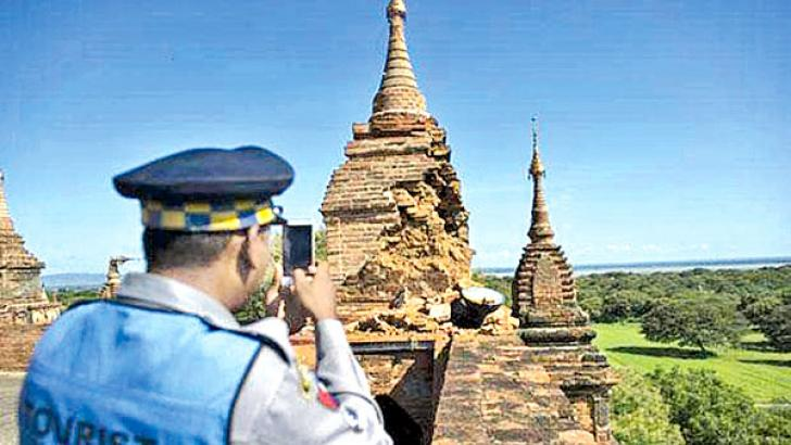 A Police officer takes a picture at the damaged, ancient Htilominlo Temple on Thursday after a 6.8 magnitude earthquake hit Bagan.