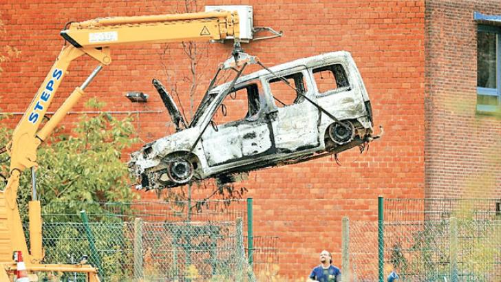 The car used to ram into the gates of Belgium's national crime laboratory, causing a fire and major damage but no casualties, is lifted up on Monday.- AFP