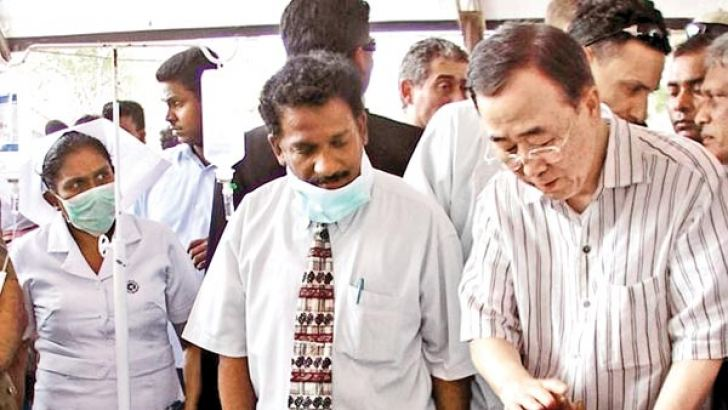 In this May 23, 2009 photo, U.N. Secretary-General Ban Ki-moon reaches out to touch a patient during a tour of a hospital at the Manik Farm refugee camp near Vavuniya.
