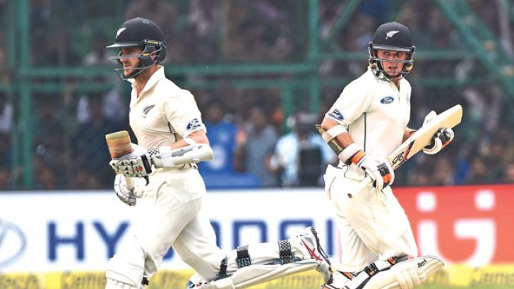 New Zealand's Tom Latham (R) and captain Kane Williamson run between the wickets during the second day of the first Test match between India and New Zealand at Green Park Stadium in Kanpur on  September 23, AFP.