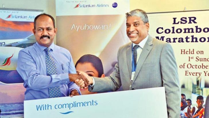 SriLankan Airlines CEO Captain Suren Ratwatte (right) hands over the sponsorship cheque to Lanka Sportreizen chairman Tilak Weerasinghe for the 16th LSR Colombo Marathon at a progress meeting at the World Trade Centre yesterday. Picture by Malan Karunaratne.