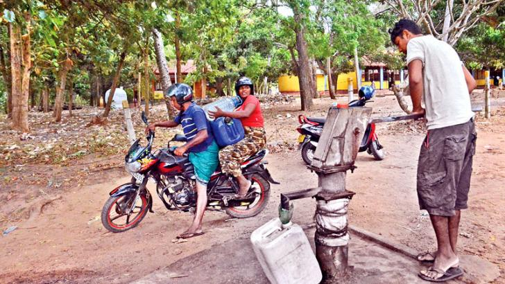 People in Puttalam hard hit by the prevalent drought have to travel a long distance to fetch drinking water from a tube well in Semmandaluwa. Here, a couple carrying cans of water drawn from a tube well on their motorcycle and a resident pumping water from the tube well. Picture by Wimal Karunatilake