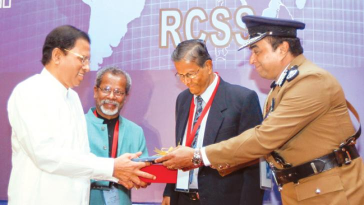 President Maithripala Sirisena receiving a memento from Inspector General of Police Pujith Jayasundara while Sri Lanka Police Commission Chairman Prof. Siri Hettige looks on.