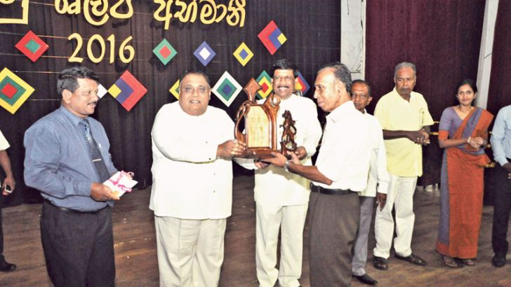 Pictured here is southern Province Chief Minister Shan Wijayalal De Silva presenting an award to a winner of the Ruhunu Shilpa Udana 2016 Southern provincial Minister of Fisheries, Rural Industries and Environmental Activities H.W.Gunasena and ministry Secretary A.U.Welarathna are also in the picture. (Picture by Mahinda P.Liyanage – Galle Central Speciaal Correspondent)