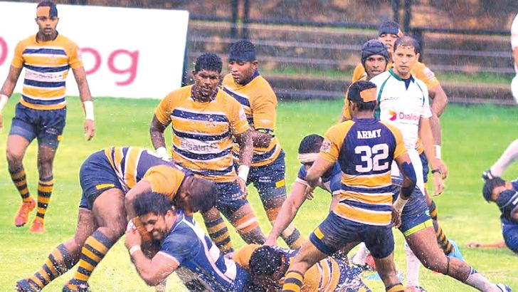 Upul Abeyratne of Army SC and Navy SC's Kanchana Perera having a terrific tussle to grab ball possession in the Clifford Cup quarterfinal match played at the Race Course Stadium yesterday. Picture by Wasitha Patabendige