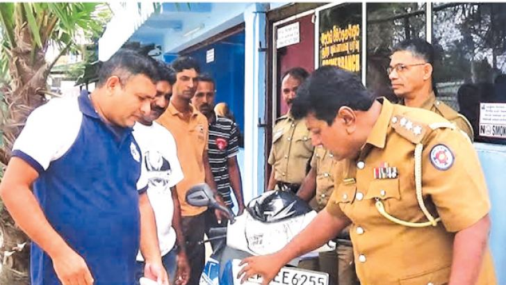 police officers inspecting the stolen motorcycle