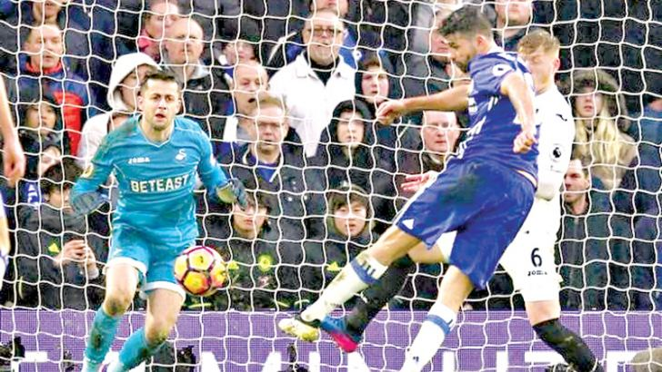 Chelsea's Diego Costa scores their third goal in their Premier League match against Swansea City at Stamford Bridge on Saturday
