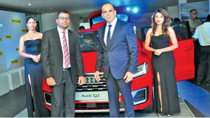 Rajieve Fernando, Director, Audi Sri Lanka and Trevine Stainwall, General Manager, Audi Sri Lanka and models posing along the new Audi Q2 SUV unveiled on Wednesday. Picture by Thushara Fernando