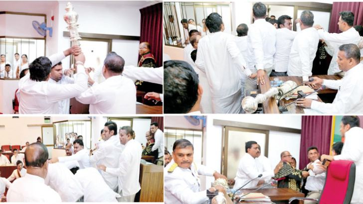 Members of the North Central Provincial Council engaging in fisticuffs at yesterday's meeting with the broken mace lying on the table. Pictures by Amila Prabath Wanasinghe