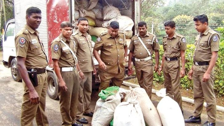 Police officers with the seized stock of tea refuse.