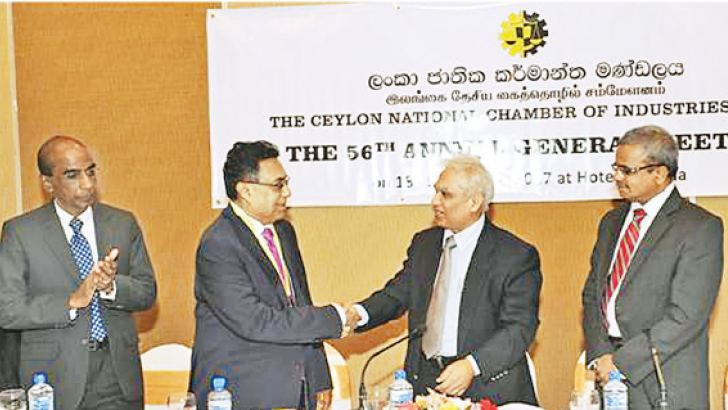 Tissa Seneviratne, the outgoing Chairman (right) congratulating the new Chairman Raja Hewabowala. Chinthaka S Lokuhetti, Secretary, Ministry of Industry and Commerce, Chief Guest of the event (right) and Gamini Gunasekera, MD, Union Chemicals Lanka PLC and CNCI's immediate Past Chairman (left) are also present. Picture by Wimal Karunathilaka