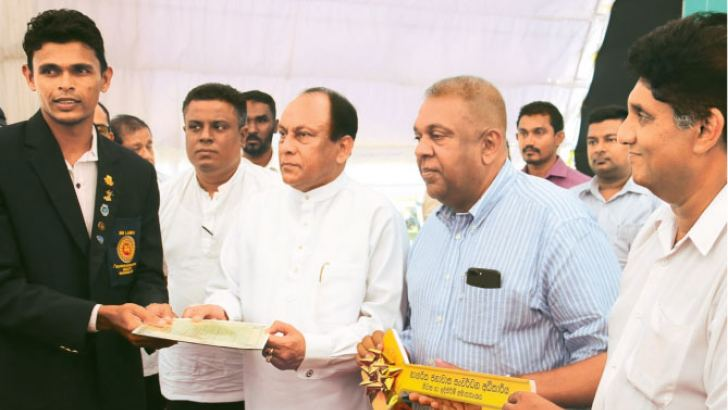 State  Minister Lakshman Yapa Abeywardena (second from left) presenting the title deed while Ministers Mangala Samaraweera and Sajith Premadasa (right extreme) handing over the key of the new house to Manjula Kumara (left extreme)