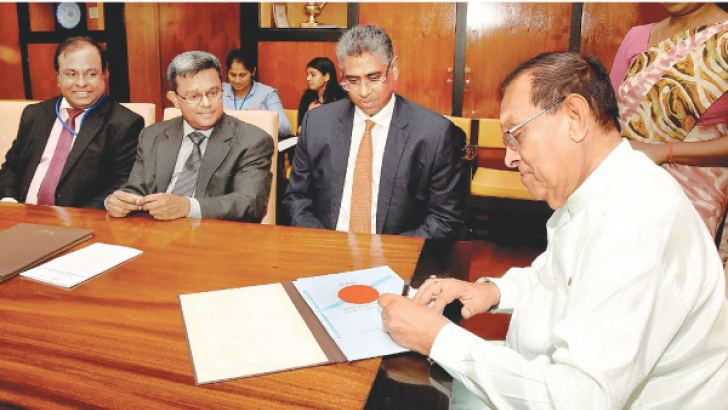 The Speaker placing his signature  to endorse the three bills to amend the Municipal Councils Ordinance,  Urban Councils Ordinance and the Pradeshiya Sabha Act No 15 of 1987,  which passed into law in Parliament. Picture by Rukmal Gamage