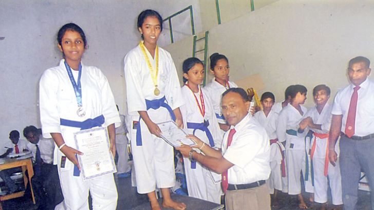 Kalathma Thilakarathna being awarded the Gold medal and the certificate at the awards Ceremony by her Master and Karate District Coach/Chief Instructor Shihan L.P. Edirisinghe.   Picture by: Kalutara Central Special Correspondent  H.L. Sunil Shantha