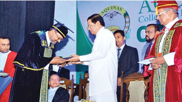 President Maithripala Sirisena presenting a token to Aquinas College Rector Susith Mark Lal Silva while Colombo Archbishop His Eminence Malcolm Cardinal Ranjith looks on.  Picture by Sudath Malaweera.