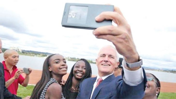 Australian Prime Minister Malcolm Turnbull takes a selfie with new Australian citizens Lydia Banda-Mukuka and Chilandu Kalobi Chilaika on Australia Day last year.