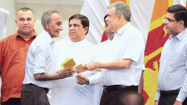Prime Minister Ranil Wickremesinghe granting a compensation payment to a flood victim in Kolonnawa. Picture by Saman Sri Wedage