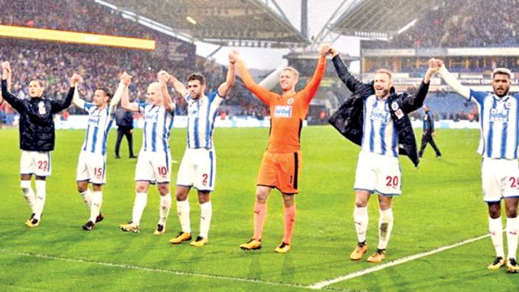 Huddersfield Town' s Jonas Lossl, Laurent Depoitre, Steve Mounie, Christopher Scindler and Mathias Jorgensen celebrate in front of their fans after victory over Manchester United.