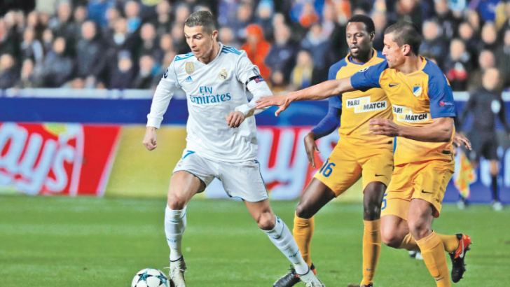 Real Madrid's forward Cristiano Ronaldo (L) is marked by Apoel's Brazilian midfielder Vinicius (C) and Apoel's Spanish midfielder Jesus Rueda (R). AFP