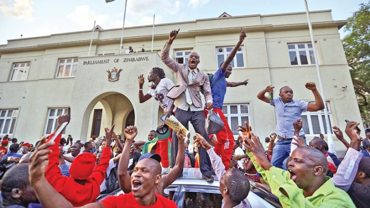 Zimbabweans celebrate outside the Parliament building in Harare.