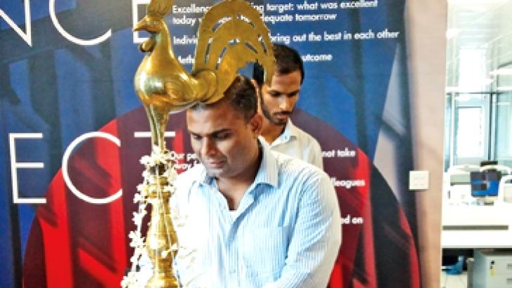 Stax Managing Director Ruwindhu Peiris lighting the traditional oil lamp at the opening.