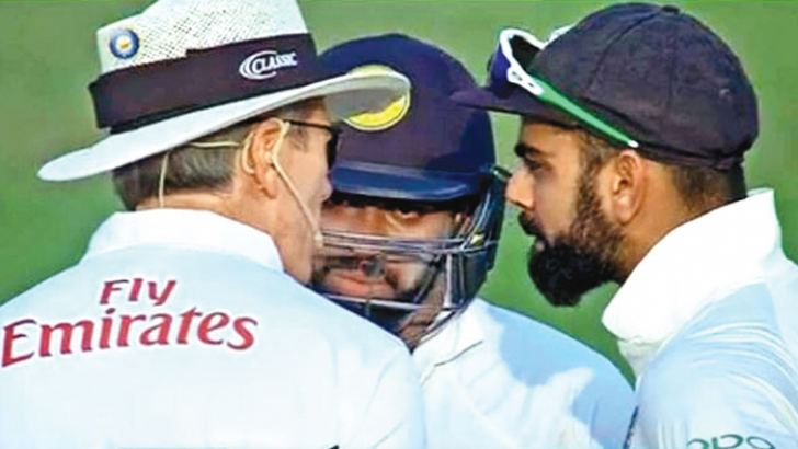 In the heat of the moment – Niroshan Dickwella and Virat Kohli is spoken to by umpire Nigel Llong during the fifth day of the first Test at Kolkata.