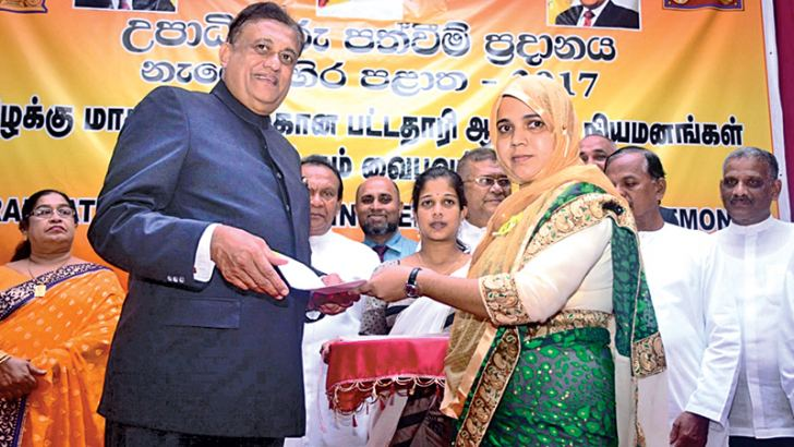 Eastern Province Governor Rohitha Bogollagama handing over an appointment letter to a graduate.