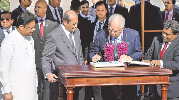 Malaysian Prime Minister Datuk Seri Najib Razak who was received by Foreign Minister Tilak Marapana is seen signing the Visitors Book at the Bandaranaike International Airport last morning. Picture by Sulochana Gamage