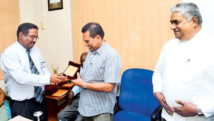 Deputy Director General of the Health Ministry Planning Division, Sathasivam Shridharan, hands over a token of appreciation to Health Minister Dr. Rajitha Senaratne while Health Deputy Minister Faizal Kassim looks on.