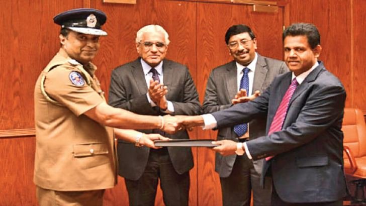Inspector General of Police, Pujith Jayasundara and Dr. H Amarathunga from FIU Sri Lanka exchanging the MOU. Dr. Indrajit Coomaraswamy, Governor and  C J P Siriwardena, Deputy Governor of the Central Bank of Sri Lanka look on.