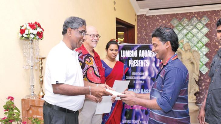 Vibhu V. Perera presenting a certificate to one of the participants of the event. Dr. Gerald Bassleer from the Netherlands and Lumbini Aquarium CEO K M Chamini Dinusha look on. Picture by Kamal Jayamanna