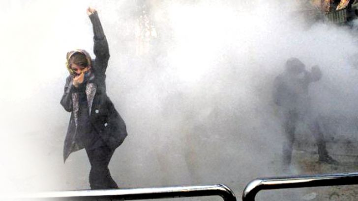 A woman raises her fist amid tear gas during a protest at the University of Tehran.- AFP