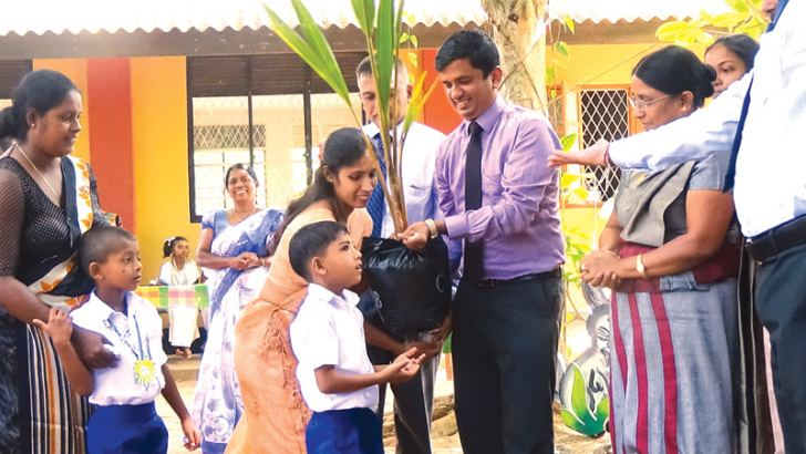 Assistant District Secretary M.M.M. Salfas distributing coconut saplings to students while the District Secretary and other officials look on.