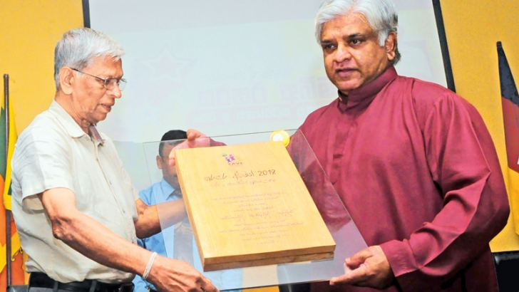 Petroleum Resources Development Minister Arjuna Ranatunga who was the chief guest presents a memento to veteran athletic coach Yogananda Wijesundera at a felicitation ceremony held at Olympic House yesterday. Pic by Wasitha Patanandige