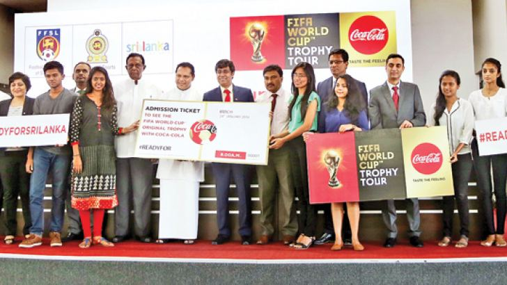 Minister of Sports Dayasiri Jayasekera and Vice President South Asia West Operations Coca Cola, Debabrata Mukherjee presenting free tickets to two young soccer fans to view the FIFA World Cup at the BMICH. Minister of Tourism John Amaratunge and secretary to the Ministry of Sports Jayantha Wijeratne are also present. Picture by Thilak Perera