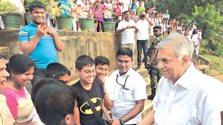 Prime Minister Ranil Wickremesinghe conversing with some students of the Kularatne Central College in Godakawela yesterday.
