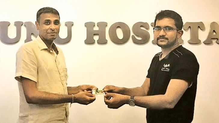 Ruhunu Hospital Co-CEO Janith Liyanage handing a Ruhunu Life Membership card to a  customer Dushan Maduranga at the hospital.