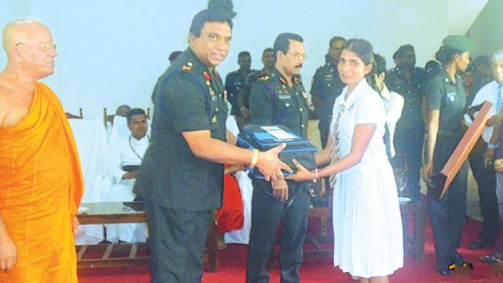 A Security Forces officer presents school accessories to a student