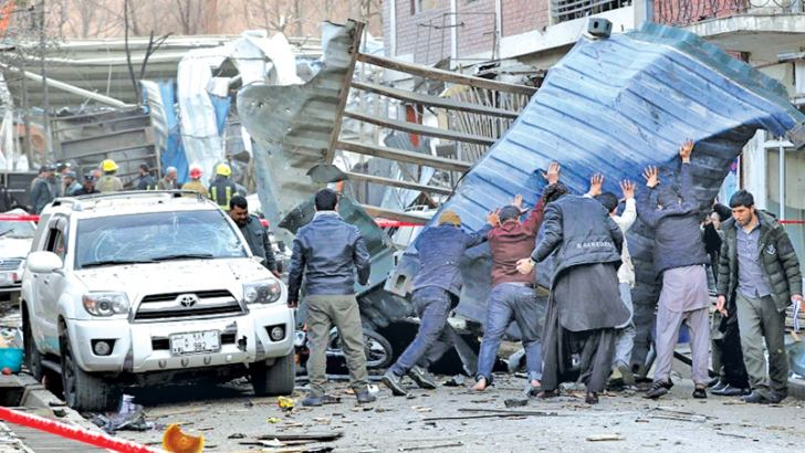 People try to remove debris from the scene of a suicide bomb attack in Kabul, Afghanistan yesterday.
